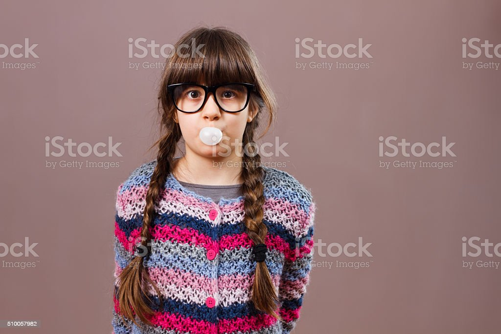 Little nerdy girl blowing bubble gum stock photo
