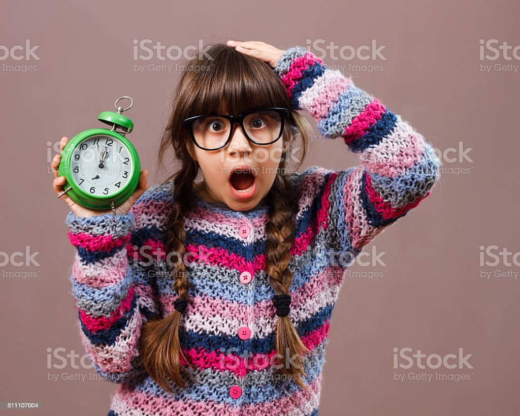 Little nerdy girl in panic holding clock stock photo