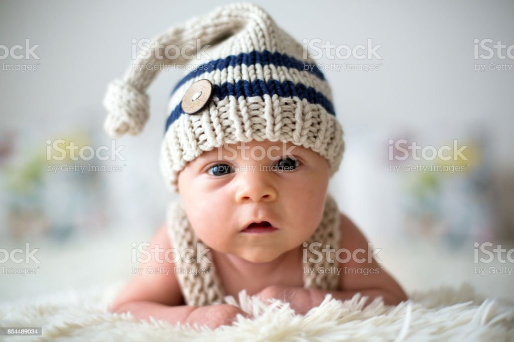 Little newborn baby boy, looking curiously at camera stock photo