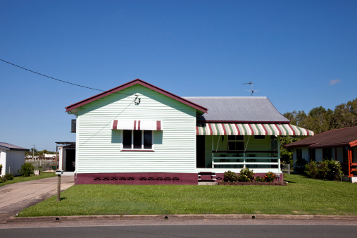 Tidy little old style house with clear blue sky and green grass and overhead power line connected to it – Queensland Australia. Click to see more...