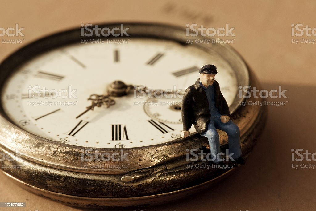 Little old man sitting on a pocket watch royalty-free stock photo