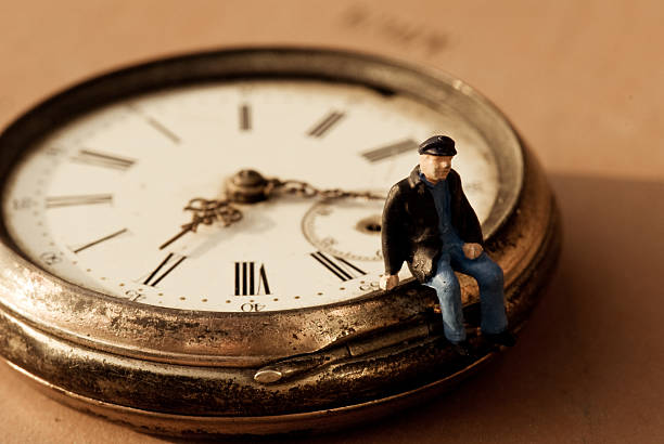 Little old man sitting on a pocket watch stock photo