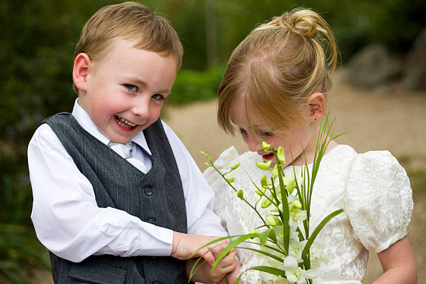 Little Page Boy Holding Hands with Flower Girl Outside stock photo