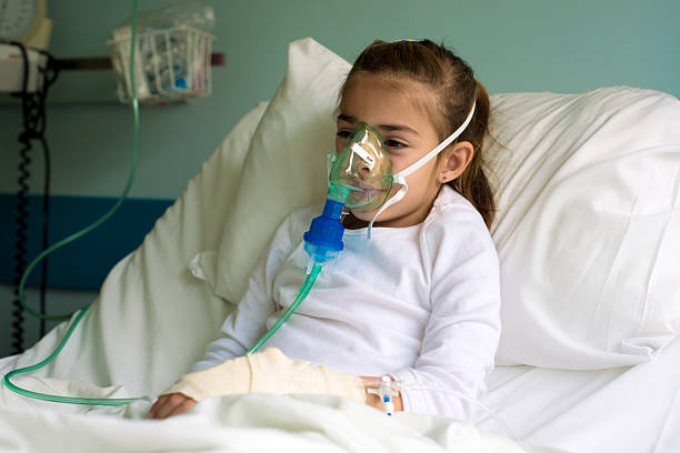 Little patient with inhalation mask Young little girl in the hospital bed using nebuliser to relieve the cough. Horizontal framing, shallow depth of field, adobeRGB photo. respiratory disease stock pictures, royalty-free photos & images