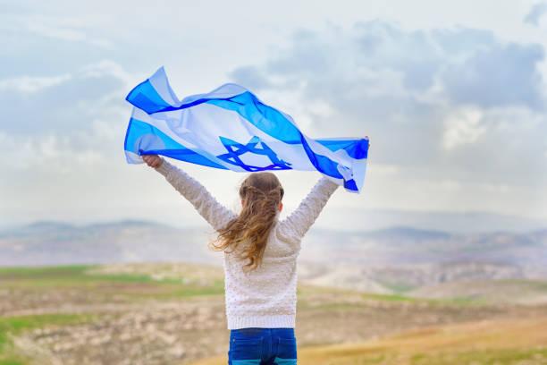 mała patriotyczna żydowska dziewczyna stojąca i ciesząca się flagą izraela na tle błękitnego nieba. dzień pamięci-yom hazikaron, patriotyczne święto dzień niepodległości izrael - koncepcja yom ha'atzmaut - judaizm zdjęcia i obrazy z banku zdjęć