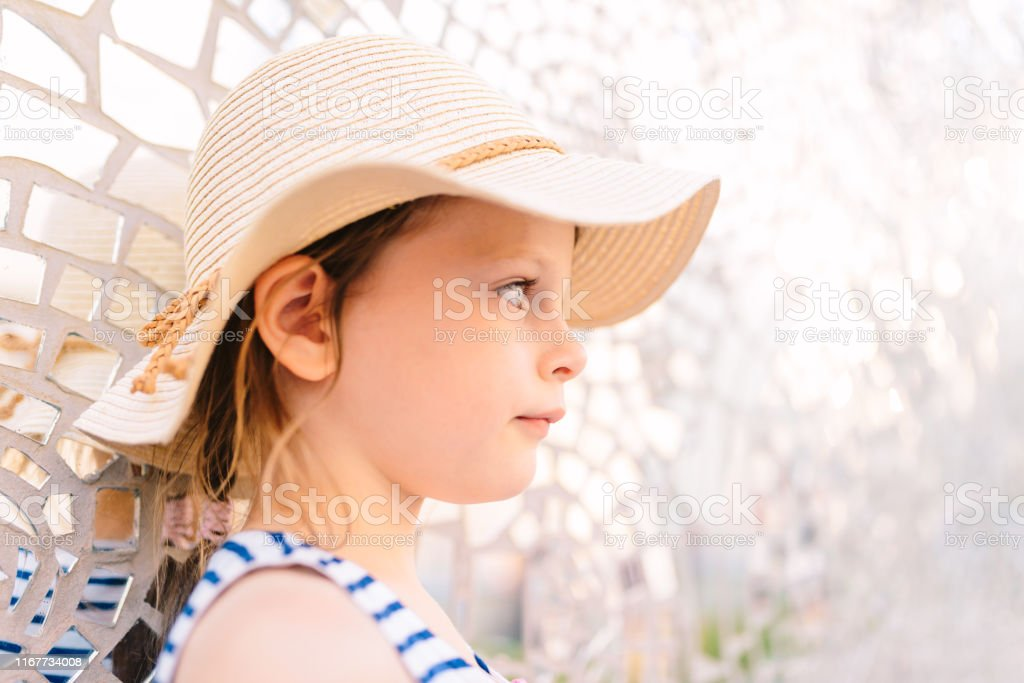 little pensive girl in a straw hat standing against the background of...