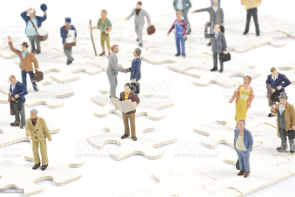 Little people on puzzle pieces figurines stock photo
