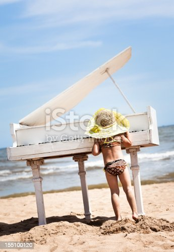 Little girl playing the piano at the beach.