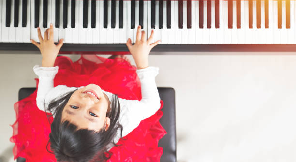 Little pianist Little asian girl happy to play piano pianist stock pictures, royalty-free photos & images