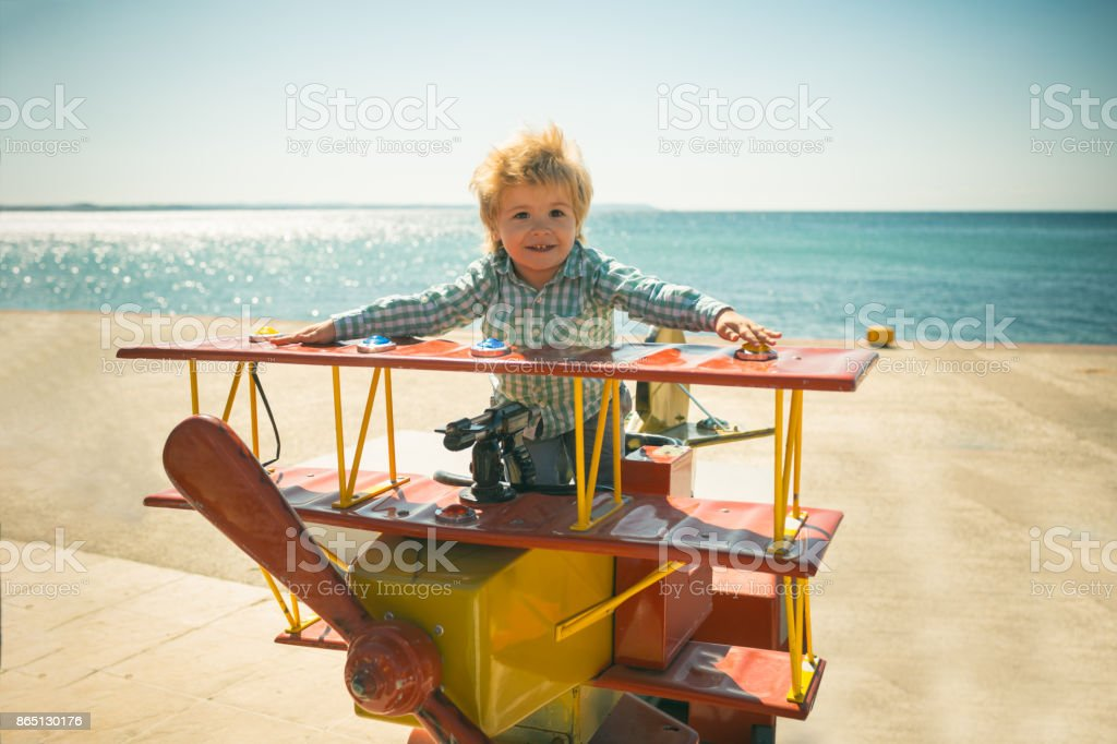 Little pilot, game on seashore. Little boy play different games on...