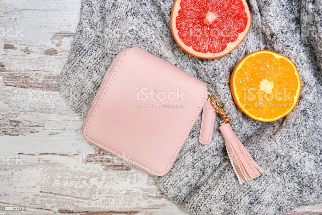 Little pink female purse, and citrus on a sweater. Fashionable concept. stock photo