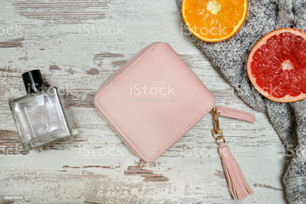 Little pink female purse, perfume and citrus on a wooden background. Fashionable concept. stock photo