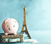 istock Little pink piggy bank on vacation. Saving for a trip to France 1149178107