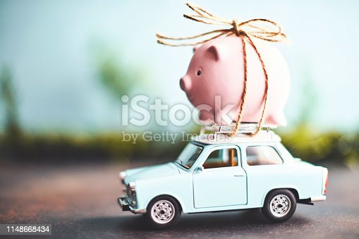 istock Little pink piggy bank tied to the top of an old car 1148668434