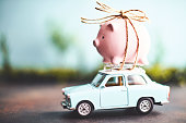 Little pink piggy bank tied to the top of an old car