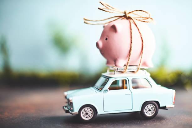 petite tirelire rose attachée au sommet d'une vieille voiture - tirelire photos et images de collection