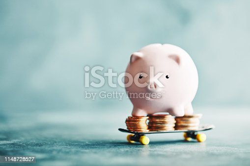 istock Little pink piggy riding on a skateboard with money 1148728527