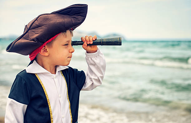 little pirate looking with spyglass - pirates stock photos and pictures
