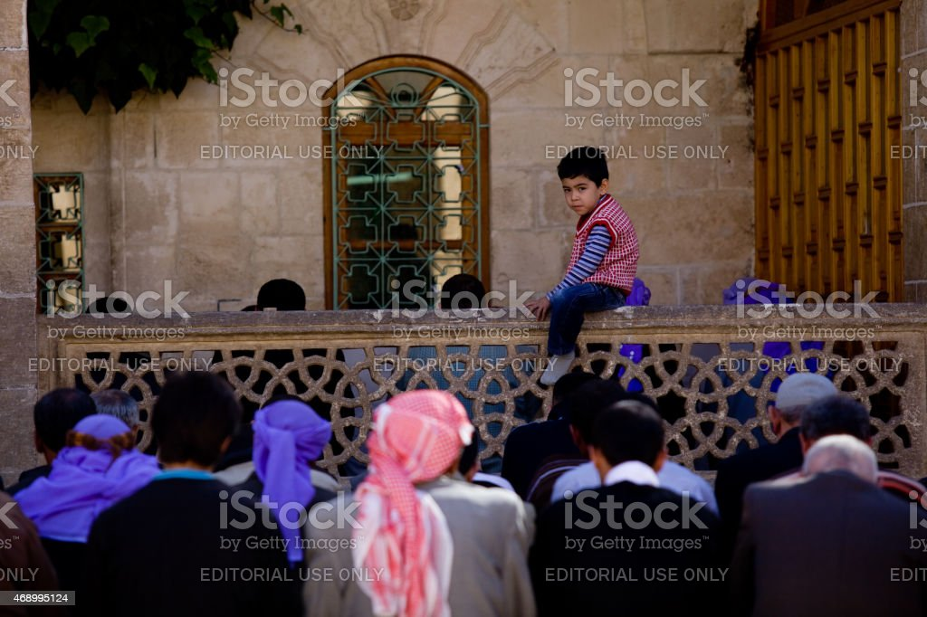 Little playful boy sitting among of praying people in friday stock photo
