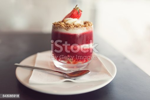Strawberry mousse served in glass with a teaspoon on the saucer