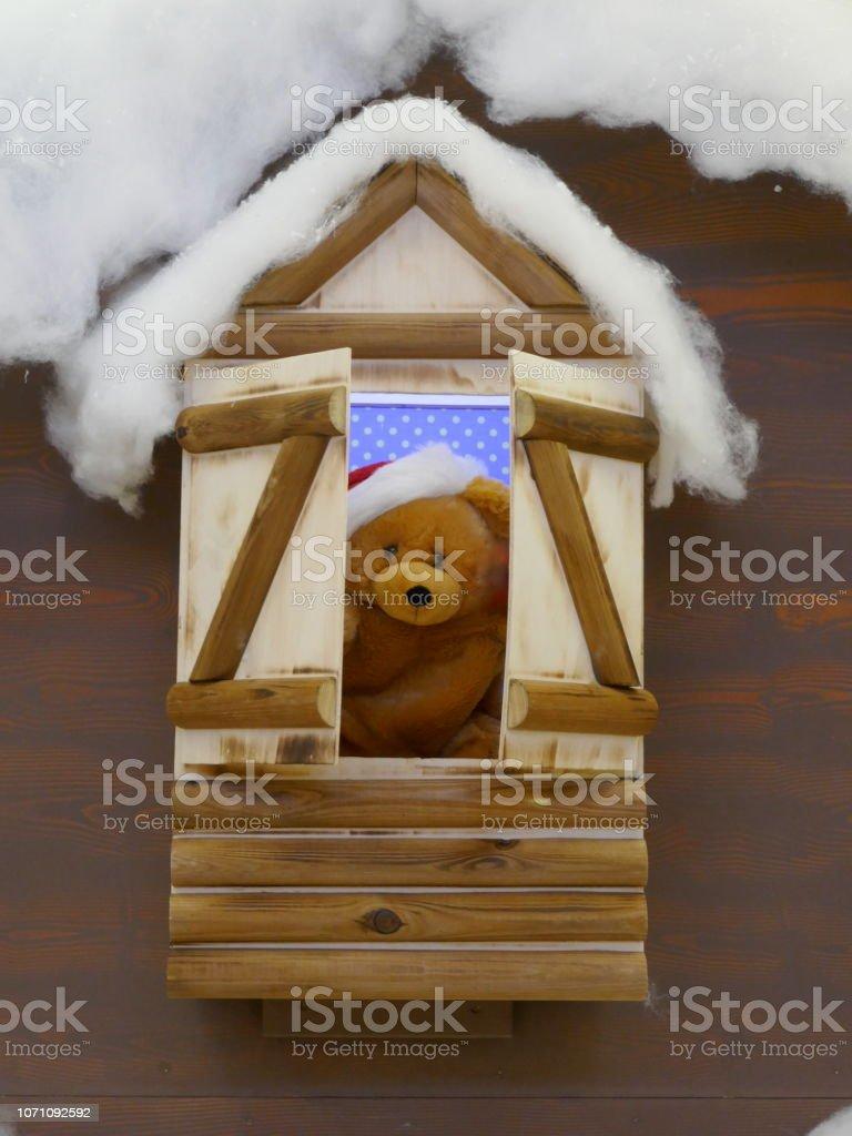 Cute little stuffed toy opens a window
