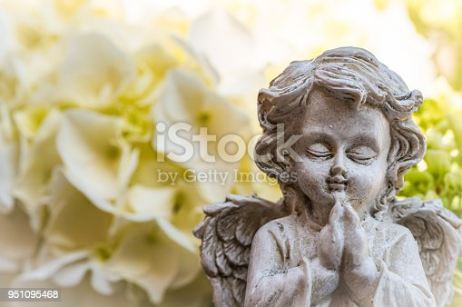 Praying angel with white flowers background and copy space