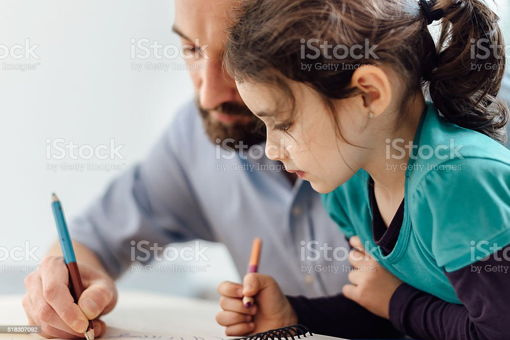 little prescholar girl and father drawing together at home stock photo