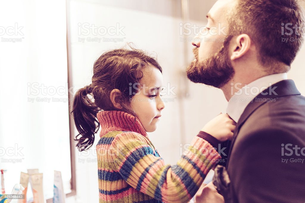 little prescholar girl binding tie to father for business outfit stock photo