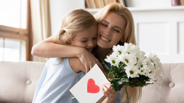 Little preschool daughter congratulating smiling mother with birthday. Joyful adorable blonde little preschool daughter congratulating smiling mother with birthday or special occasion, presenting flowers and handmade card. Thankful young mommy cuddling child girl. birthday wishes for daughter stock pictures, royalty-free photos & images