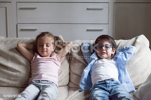 istock Little preschool girl and boy relaxing sitting on couch 1070079138