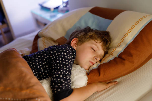 Little preschool kid boy sleeping in bed with colorful lamp. Little preschool kid boy sleeping in bed with colorful lamp. School child dreaming and holding plush toy. Kid angry of darkness. bedtime stock pictures, royalty-free photos & images
