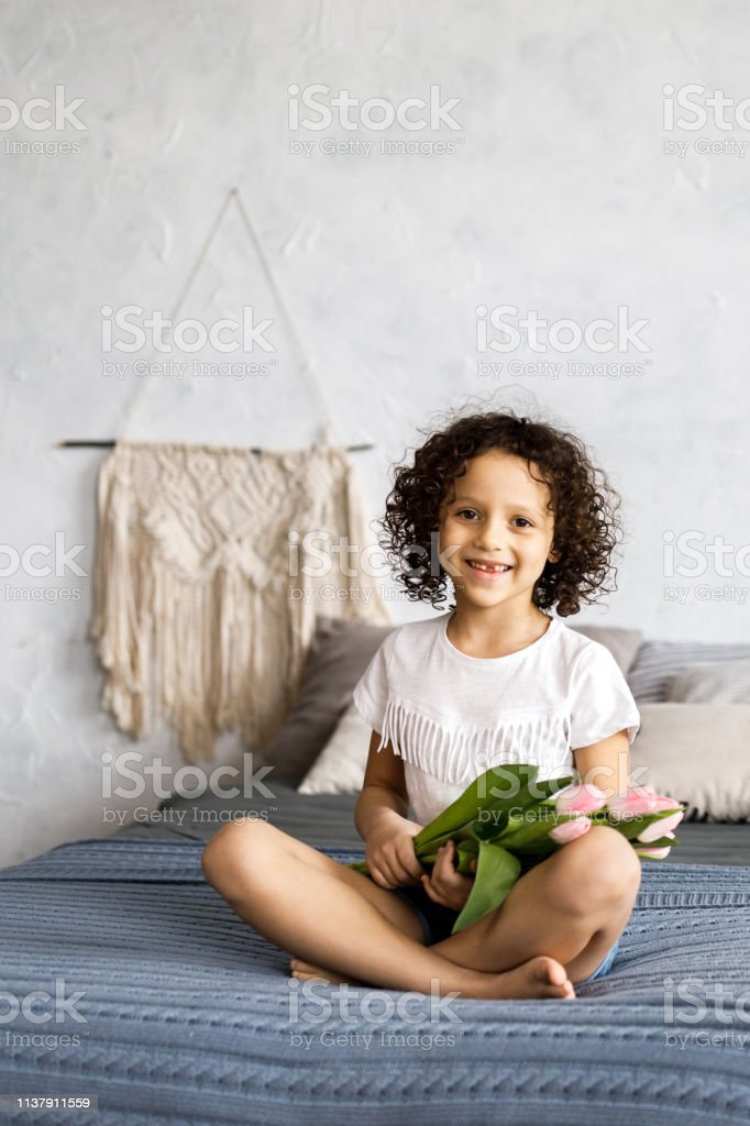 A little pretty curly girl sitting on her bed with tulips in her arms.
