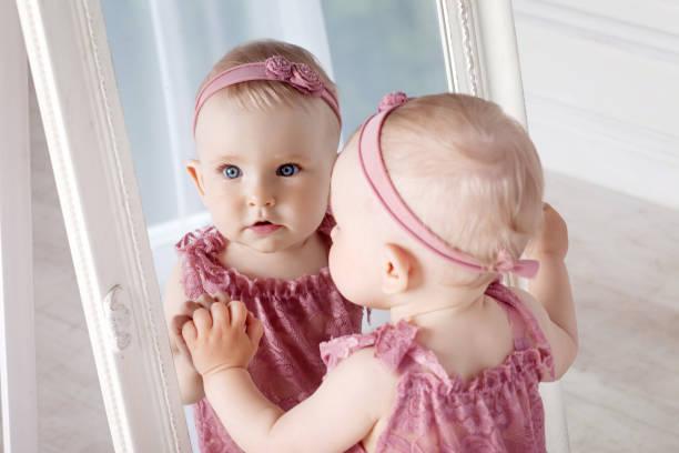 kleines hübsches mädchen spielt mit einem großen spiegel. porträt des kleinen mädchens mit reflexion in einem spiegel - prinzessin kleid kind stock-fotos und bilder