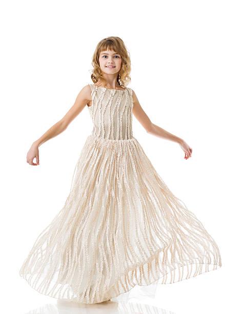 Little princess dancing in long beige dress stock photo