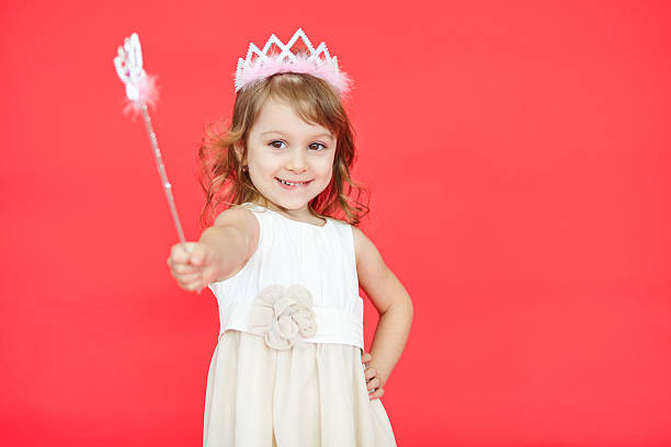 little princess girl pointing her magic wand towards camera - fairy wand stock photos and pictures