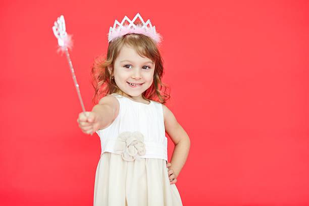 kleine prinzessin mädchen zeigt ihre zauberstab in richtung kamera - prinzessin kleid kind stock-fotos und bilder