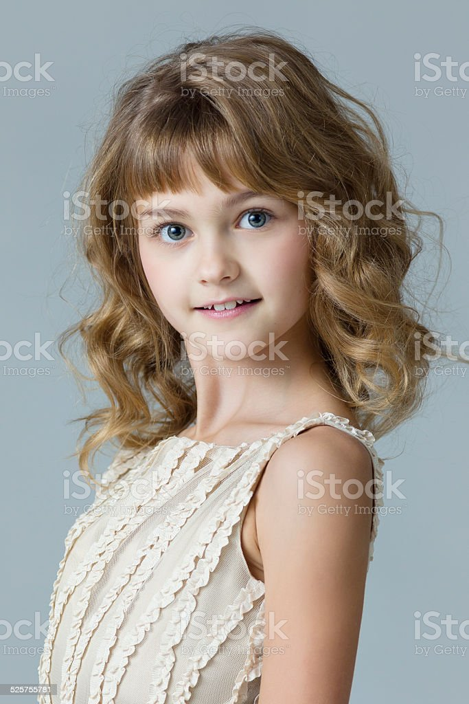 Little princess in beige dress on gray stock photo