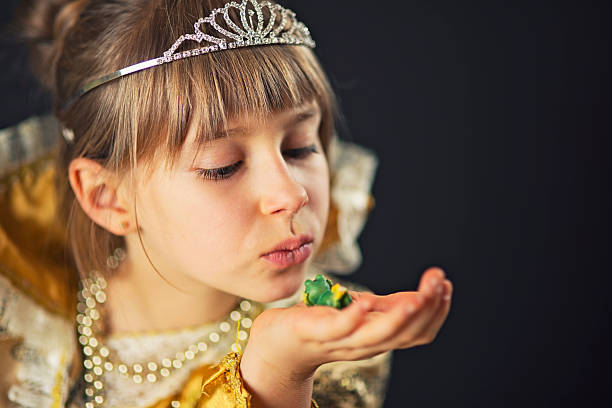 kleine prinzessin mit frosch küssen - prinzessin tiara stock-fotos und bilder