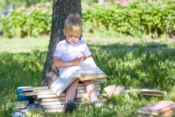 little prodigy boy is reading big book in garden. staircase and steps of books - education, knowledge, and people concept education, knowledge, and people concept - little prodigy Boy is reading big book in garden. Staircase and Steps of Books child prodigy stock pictures, royalty-free photos & images