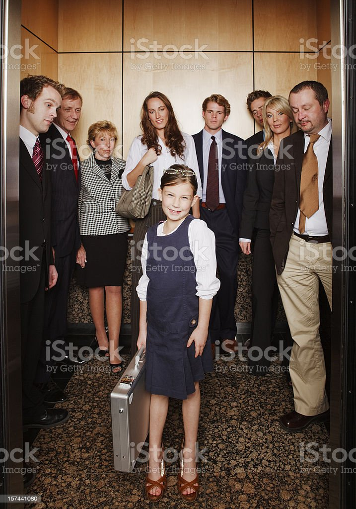 Little proud power girl stepping out of a filled elevator stock photo