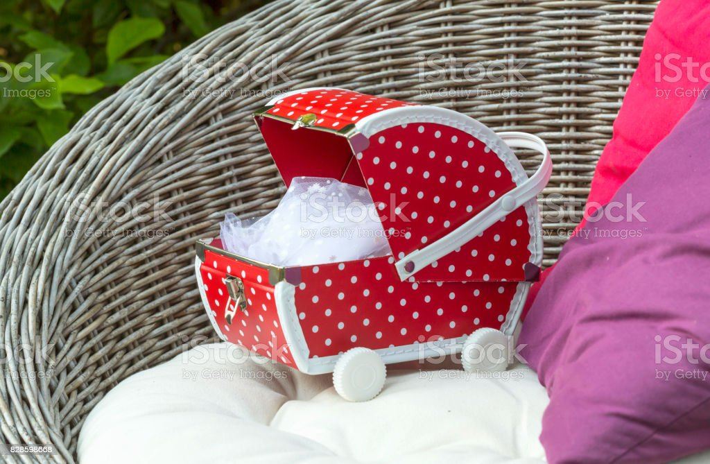 Little red doll buggy on a chair. stock photo