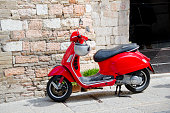 Assissi, Italy - April 19, 2015:  A red Italian scooter or moped sits outside a centuries old home in a small Italian hill town...the proverbial picture of small town Italian life!