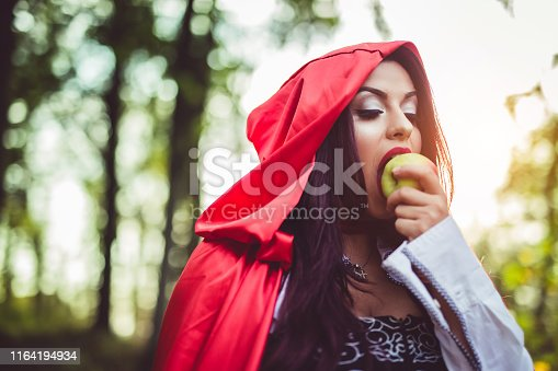 Close up picture of a Little red riding hood in the forest eating an apple. Day time.