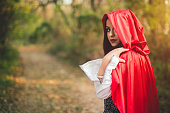 Little red riding hood looking towards sunset, seems to be lost in the forest. Waist up.