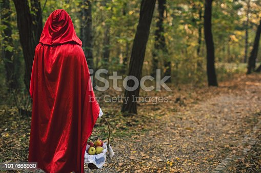 Woman dressed like little red riding hood poses in a forest with apples