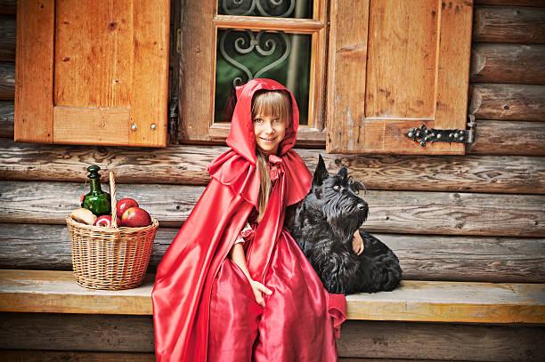 rotkäppchen vor einem cottage - rotkäppchen kostüm stock-fotos und bilder