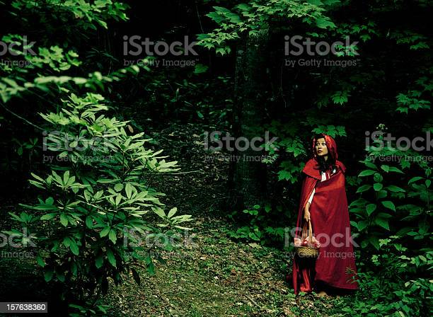 not so Little Red Riding Hood lost in the forest, looking over her shoulder worried about a predator