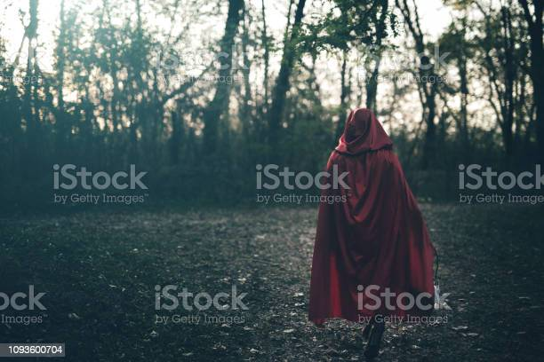 Woman dressed as little red riding hood carrying basket with apples