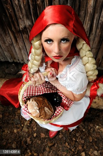 Little Red Riding Hood Lost In The Forest Sitting On A Log Looking Frightened