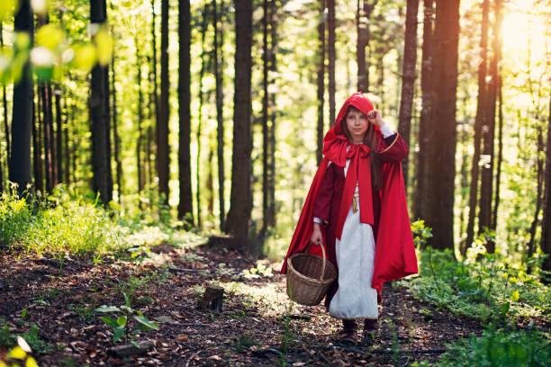 little red riding hood im wald wandern - rotkäppchen kostüm stock-fotos und bilder